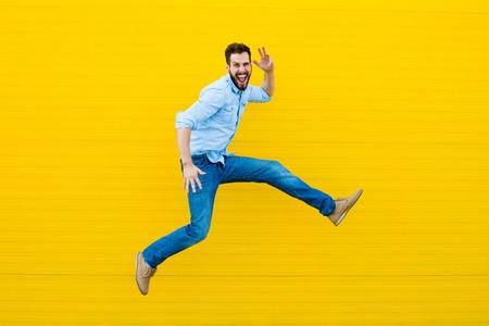 ハンサムな男のカジュアルな服装を祝うと、黄色の背景にジャンプ