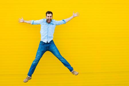 vzrušený: pohledný muž ležérní oblečení slaví a skákání na žlutém pozadí