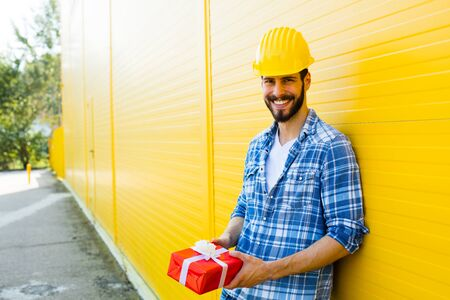plaid shirt: adult worker with yellow helmet and plaid shirt next to a wall smiling with a gift in hands
