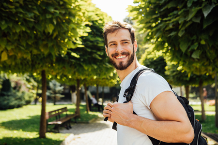 ni�o con mochila: close up handsome student having  backpack standing outside