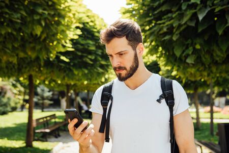beautiful boys: handsome student having  backpack and talking at mobile phone standing outside