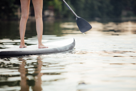 clouse-up of a woman legs on paddleboard in water