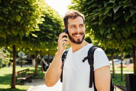 oportunity: handsome student having  backpack and talking at mobile phone standing outside