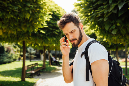 handsome student having  backpack and talking at mobile phone standing outside