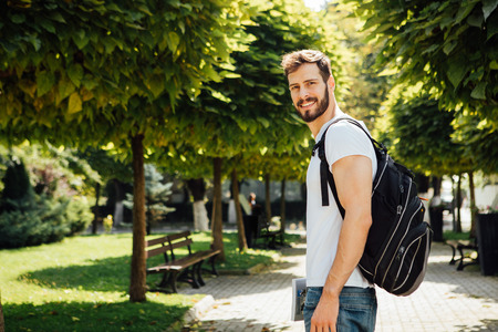 handsome student having books in hands and backpack standing outside