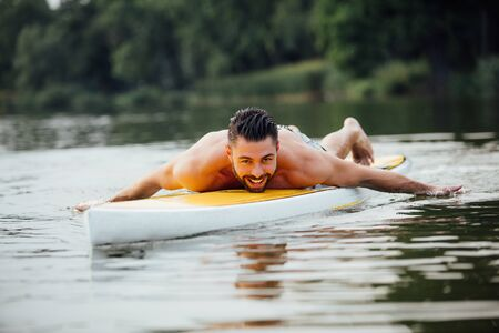 paddleboard: handsome athletic man swimming on a paddleboard and smiling, lake surrounded by trees Stock Photo