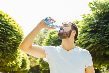tomando agua: Primer plano de un hombre de agua potable de una botella fuera Foto de archivo