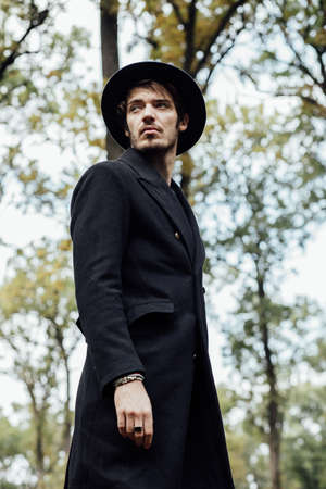 shivering: young man with black hat walkink in forest