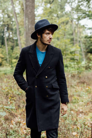 clothing model: young man with black hat walkink in forest