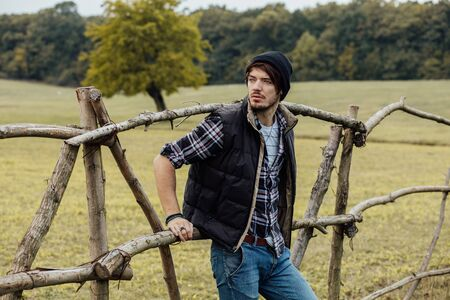sexy cowboy: young sexy country boy next to a wooden fence, standing outside in nature