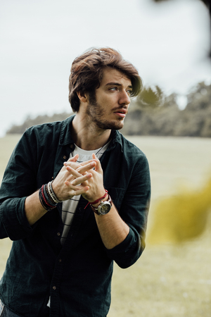 atractive: sexy handsome man standing on a field, autum mood