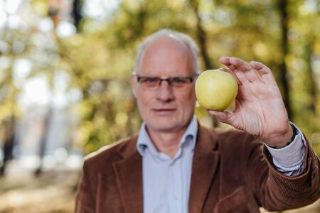 longevity medicine: senior adult with gray hair and eyeglasses, elegant dressed, showing an green apple standing outside Stock Photo