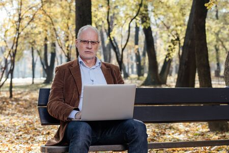 socialization: old businessmen sitting outside on a bench and working at laptop