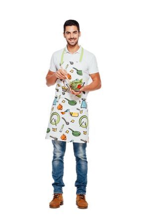 handsome man in kitchen apron and bowl of salad isolated on white