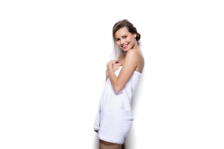 beautiful young woman with bath towel on the body against a white wall Banque d'images