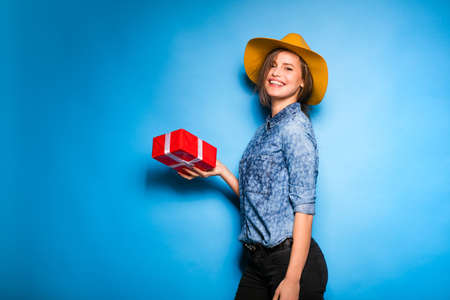 studio model: young modern woman holding a red gift in hands, on blue background