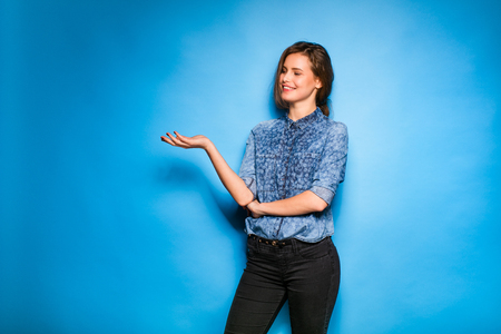 blue face: young woman casual dressed standing on a blue background