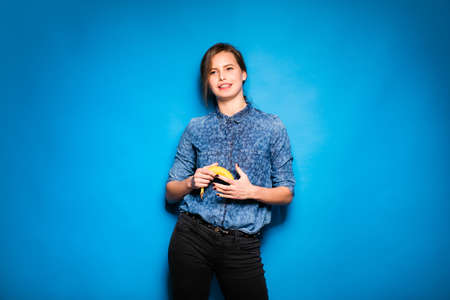 the weakening: young modern woman holding a banana in hands on blue background Stock Photo