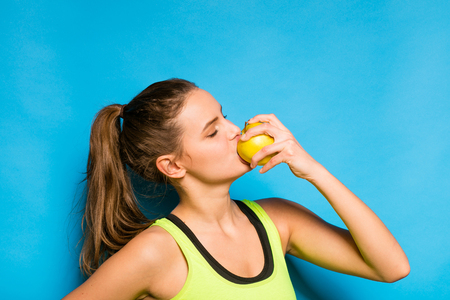 fit girl: pretty young woman in fitness equipment eating and apple on blue background