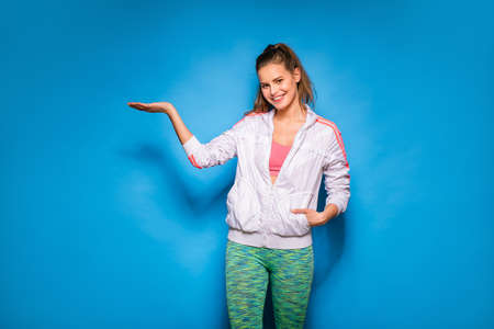 something athletic: young athletic woman in white hoodie standing and showing something on blue background
