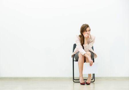Femme dans le bureau tenue assis sur une chaise avec des feuilles de papier à la main et de la pensée Banque d'images - 51922267