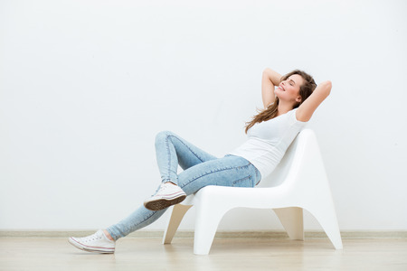 single happy young woman sitting on a white chair in an empty room, thinking on something