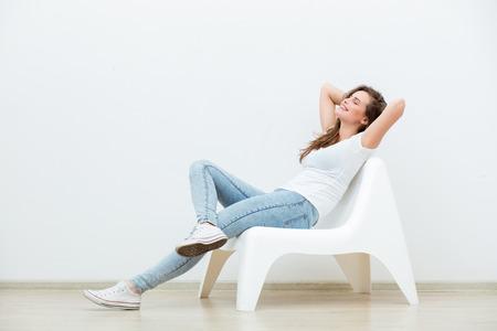 sola mujer joven feliz sentado en una silla blanca en una habitación vacía, pensando en algo