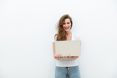 young beautiful modern woman having an laptop in hands, leaning on a white wall, happy