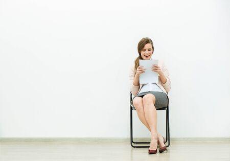 vrouw in office outfit zittend in een stoel met enkele vellen papier in de hand en denken