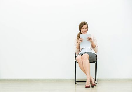 woman in office outfit sitting in a chair with some sheets of paper in hand and thinking Фото со стока