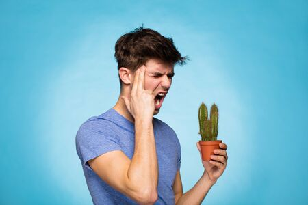 unbearable: concept with a young man in T-shirt, holding in hand a cactus suggesting pain Stock Photo