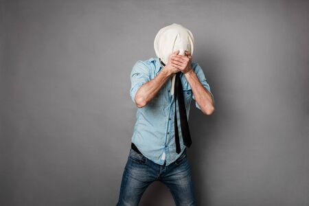 unrecognisable person: concept with a young man with face covered by a textile material acting normal but having no face, on grey Stock Photo