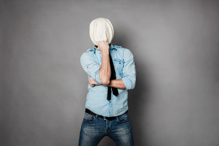 face covered: concept with a young man with face covered by a textile material acting normal but having no face, on grey Stock Photo
