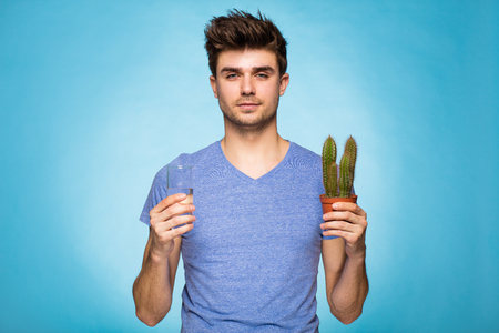 unbearable: concept with a young man in T-shirt, holding in hand cactus suggesting pain and a glace of water Stock Photo