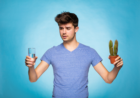 suggesting: concept with a young man in T-shirt, holding in hand cactus suggesting pain and a glace of water Stock Photo
