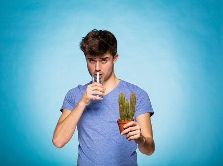 unbearable: concept with a young man in T-shirt, drinking water with a cactus in hand