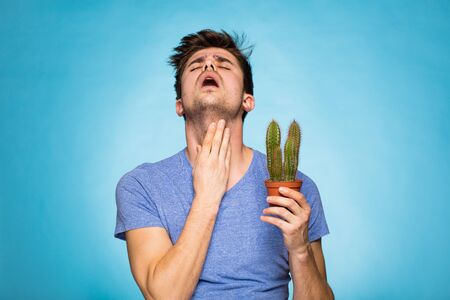 suggesting: concept with a young man in T-shirt, holding in hand a cactus suggesting pain Stock Photo
