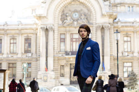 bussiness time: elegant man standing outside, with a classic building on background