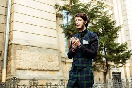 bussiness time: elegant man standing outside, wearing green plaid costume