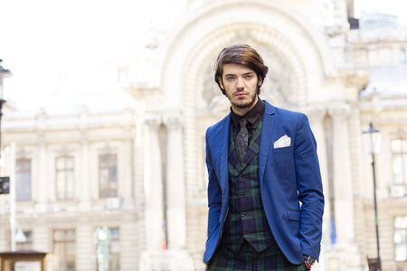 bussiness man: elegant man standing outside, with a classic building on background
