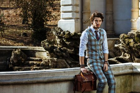 genuine leather: elegant man standing outside, wearing plaid costume and a genuine leather bag
