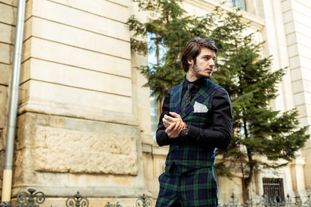 elegant man standing outside, wearing green plaid costume