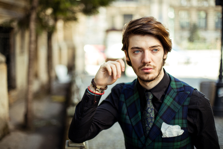bussiness time: clouse up of an elegant man standing outside, wearing green plaid costume