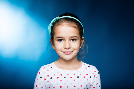 attitude girls: little girl with green headband with bow, smiling Stock Photo