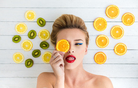 beautiful blonde woman laying on a white wooden table next to slices of orange, lemon and kiwi