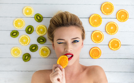 beautiful blonde woman laying on a white wooden table next to slices of orange, lemon and kiwi. Taking a bite