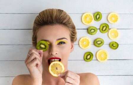 fruits juice: beautiful blonde woman laying on a white wooden table next to slices of lemon and kiwi Stock Photo