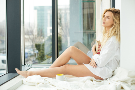 open windows: beautiful blonde woman sitting comfortably on a balcony, wearing mens shirt holding a book and coffee