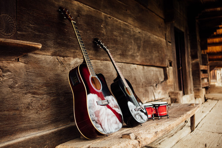 bongos: guitar leaning on a old wooden porch Stock Photo