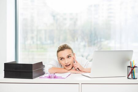 telephone interview: blonde woman lying on her desk and thinking at solutions Stock Photo